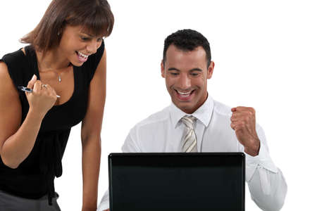 delighted: Young business couple at a laptop Stock Photo