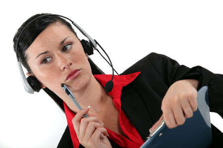 receptionist with headset and side look taking a call photo