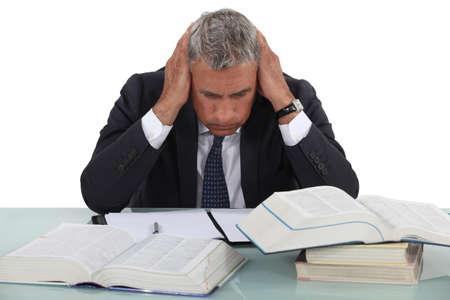 scholarly: Stressed man sat at desk Stock Photo