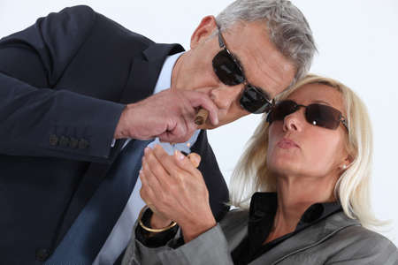 mature gentleman smoking cigar with blonde spouse showing off photo