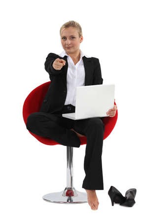 Businesswoman sitting in a chair and pointing her index finger photo