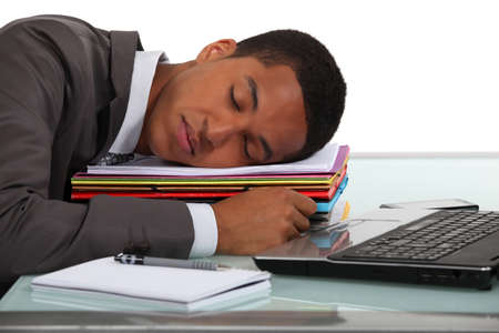 over burdened: Businessman asleep at his desk
