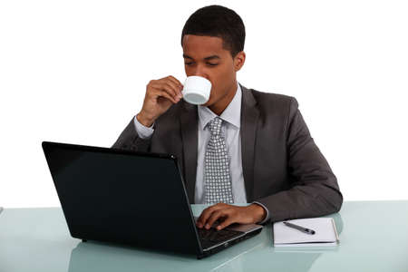 office force: young Afro-American businessman working on his laptop and drinking his coffee Stock Photo