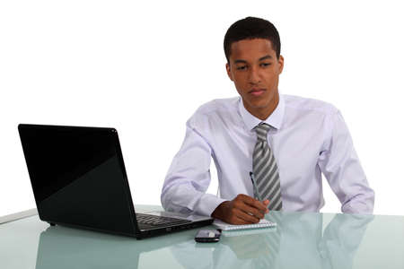Man sat at desk writing on pad Stock Photo - 15915762
