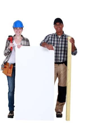 Construction workers holding white panel photo