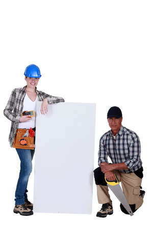tradeswoman: A team of tradespeople standing around a blank sign