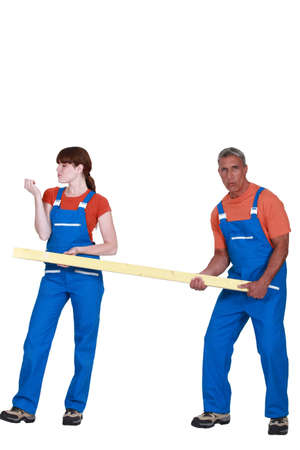 jumpsuit: Construction couple carrying timber