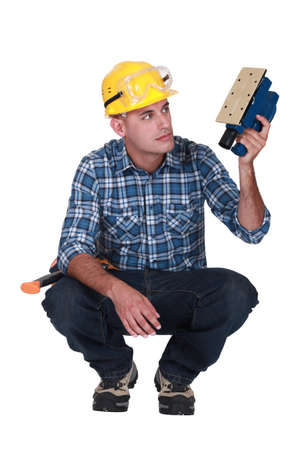 to crouch: Worker with an electric sander