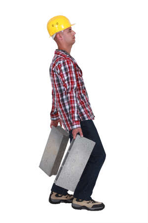carries: Man carrying two heavy building blocks Stock Photo