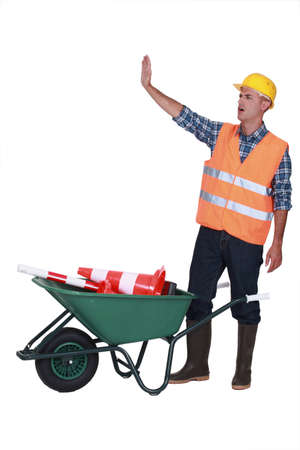 Builder making stop gesture whilst stood with traffic cones photo