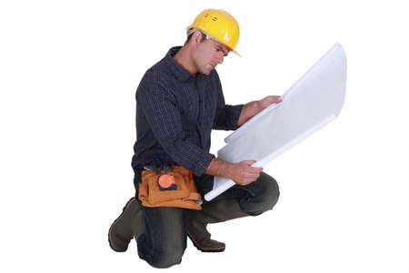 kneel: Frowning tradesman examining a blueprint