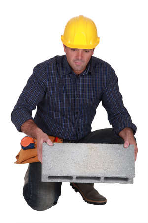 stonemasonry: Tradesman holding a clinker block Stock Photo