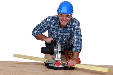 A carpenter with a circular saw  photo