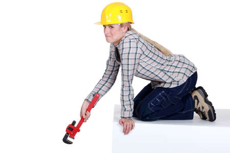 Unhappy tradeswoman holding a pipe wrench Stock Photo - 15915726