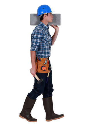 Tradesman carrying a cinder block Stock Photo