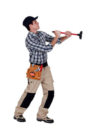 unplugging: A plumber unplugging the wall  Stock Photo