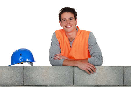 leveler: Young mason stood by wall Stock Photo