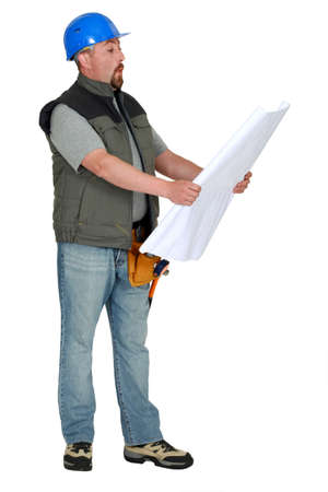 Tradesman examining a blueprint photo