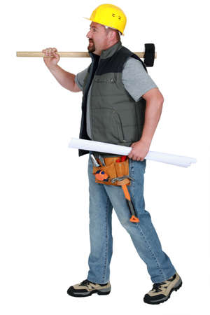 Tradesman carrying a mallet and a blueprint photo