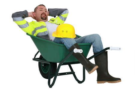 Man taking a snooze in a wheelbarrow photo