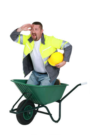 Construction worker in a wheelbarrow Stock Photo - 15915643