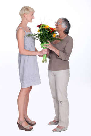 Young woman giving an elderly lady flowers photo