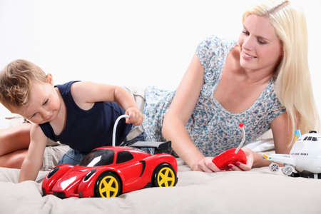 babysitting: Toddler and mum playing with a remote controlled sports car
