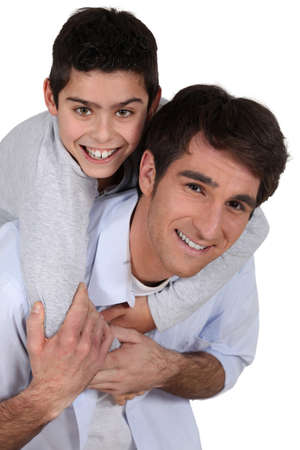 single parents: father giving young son piggyback Stock Photo