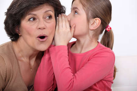 Girl whispering a secret to her grandmother photo