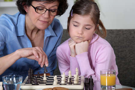 Young girl playing chess with grandma photo