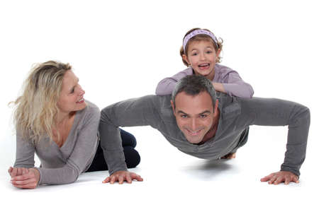 Father doing push-up with daughter on back photo