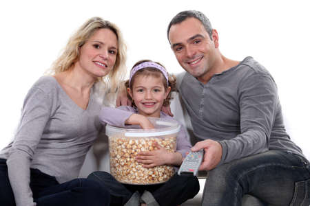 bowl of popcorn: Family with a huge tub of popcorn