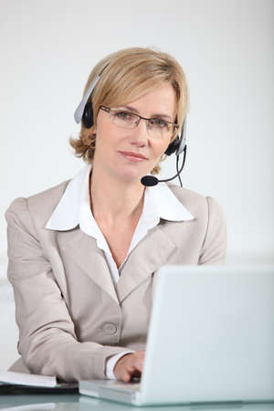 Woman with headset on laptop photo