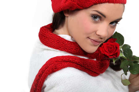 red scarf: Brunette holding rose to face