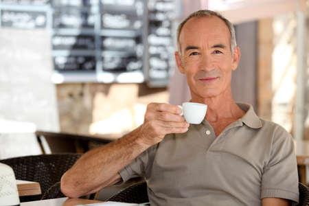 caf: Elderly man having an espresso on a terrace
