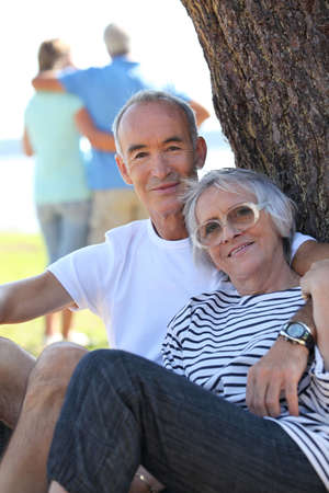 60 64 years: Senior couple  sitting by a tree in the summertime Stock Photo