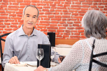 65 years old: Senior couple eating a meal in a restaurant