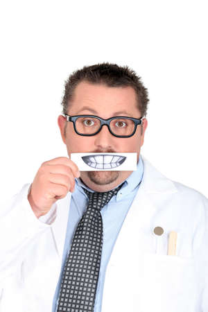 Male dentist holding picture of teeth photo