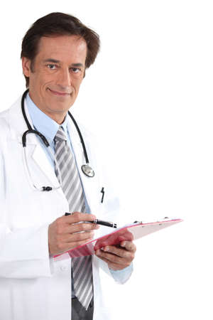 50 to 60: Doctor smiling with clipboard Stock Photo