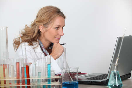 Blond researcher in lab using laptop computer