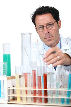 precipitate: 50 years old scientist in a lab behind test tubes