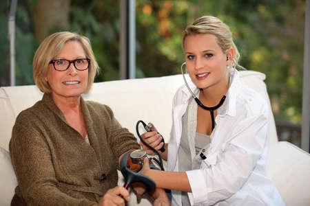 home healthcare: doctor examining a senior woman