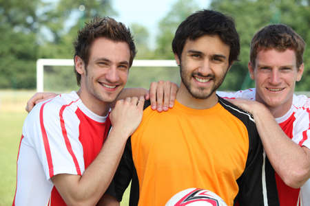 three day beard: Three young football players on a football field
