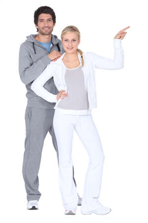 Couple wearing tracksuits pointing off camera photo