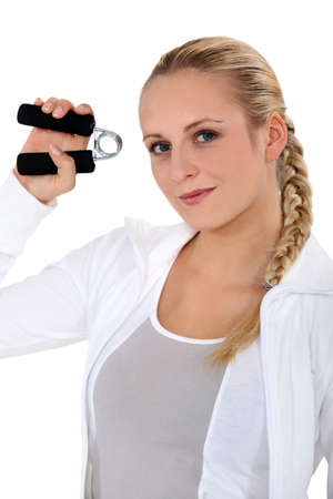 hand grip: Woman using hand grippers at the gym Stock Photo