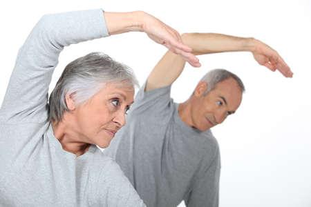 estiramientos: Senior pareja estiramiento en el gimnasio Foto de archivo