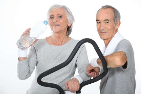 physical activity: Elderly couple working out together in gym