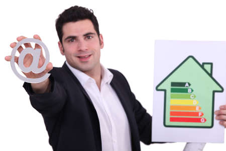 architect holding at sign and picture showing house with energy rating Stock Photo - 15915609