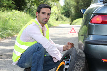 40s: Man changing a tyre at the side of the road Stock Photo