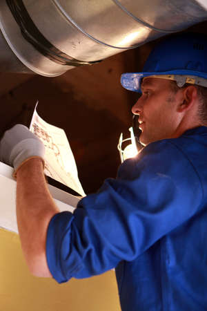 complex system: Worker repairing ventilation system